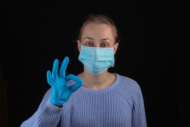 의료 얼굴 마스크와 장갑에 여자는 검은 벽에 좋아요 기호를 보여줍니다. 공황 중지
