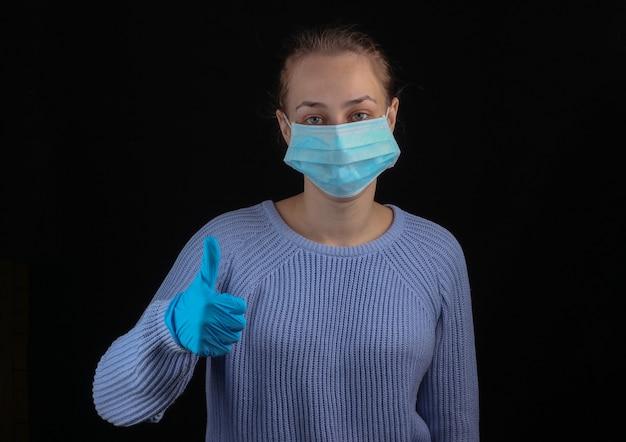 医療用フェイスマスクと手袋を着用した女性は、黒い壁に親指を立てています。
