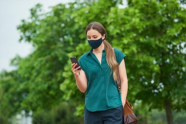 의료 얼굴 마스크에 여자는 공원에서 산책 바지 주머니에 손을 밀어 스마트 폰 뉴스를 읽습니다