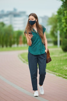 의료 얼굴 마스크에 여자는 바지의 주머니에 손을 밀어 스마트 폰 뉴스를 읽고 공원에서 산책