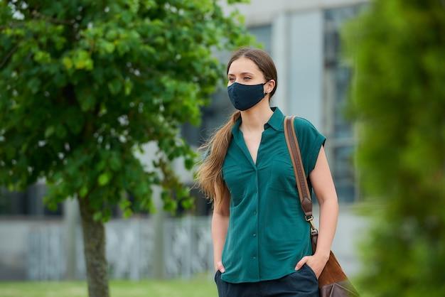 의료 얼굴 마스크에 여자 바지 주머니에 손을 밀어 나무 사이 산책, 시내에서 가방을 보유하고