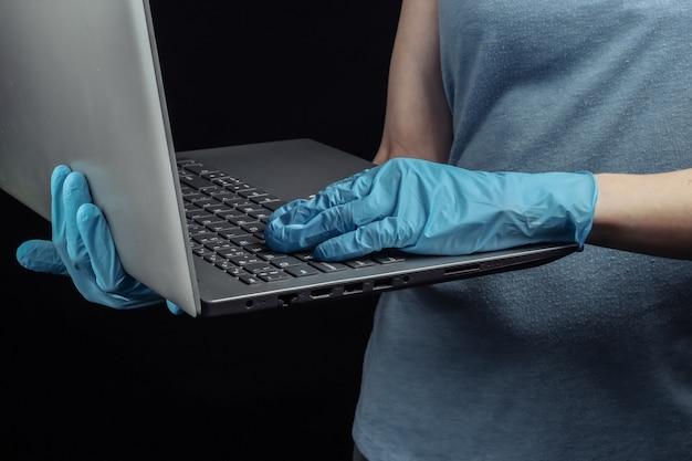 Женщина в медицинских перчатках держит ноутбук на черной стене.