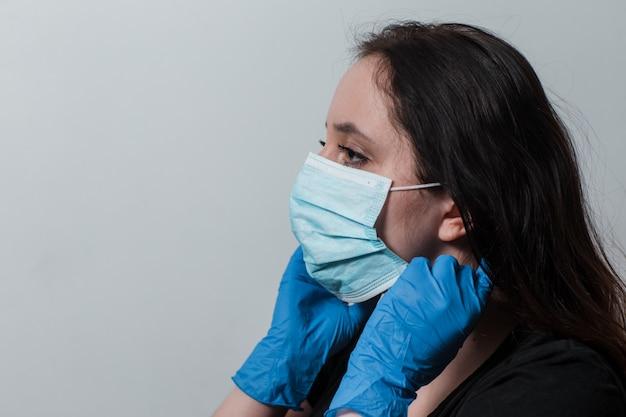 医療用手袋の女性は防護マスクを置く
