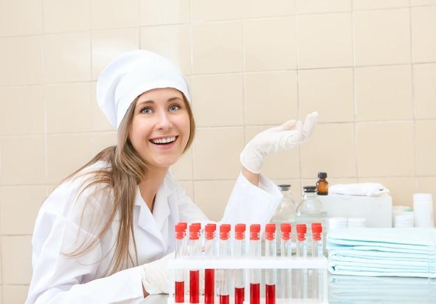 血のチューブを持つ医療用ガウンの女性