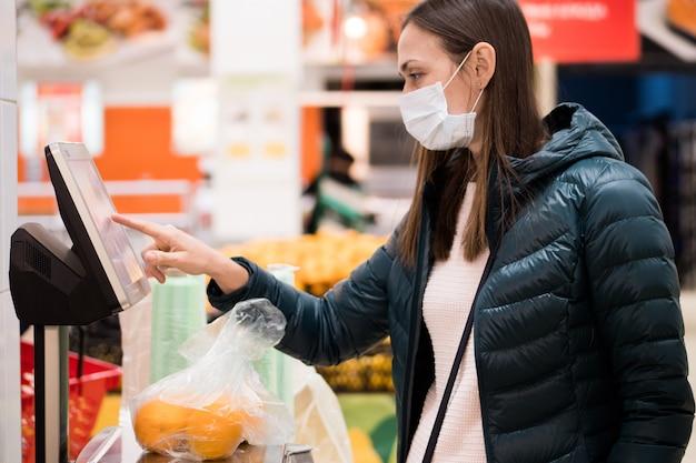 医療マスクの女性のスーパーマーケットのスケールでオレンジの重量を量る