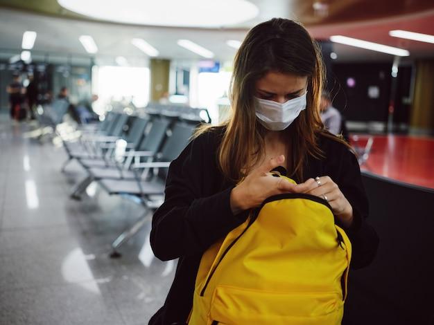 黄色のバックパックを待っている医療マスクと空港の女性