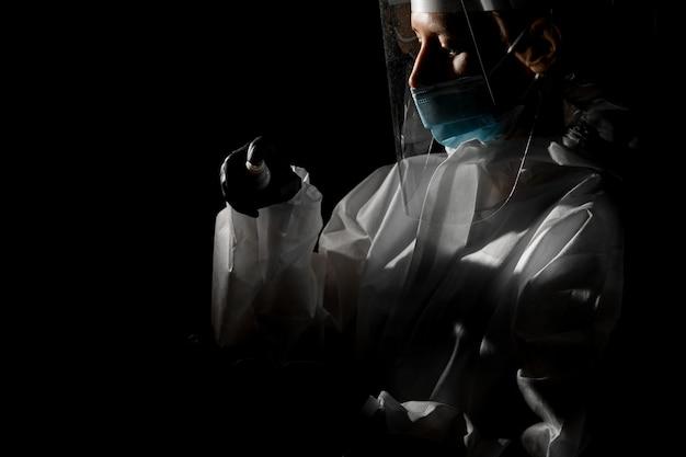Женщина в медицинской маске и защитном щите на голове собирается распылять дезинфицирующее средство на руках