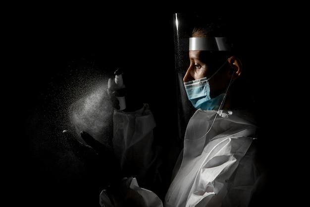 Женщина в медицинской маске и защитном щите на голове распыляет дезинфицирующее средство на руки