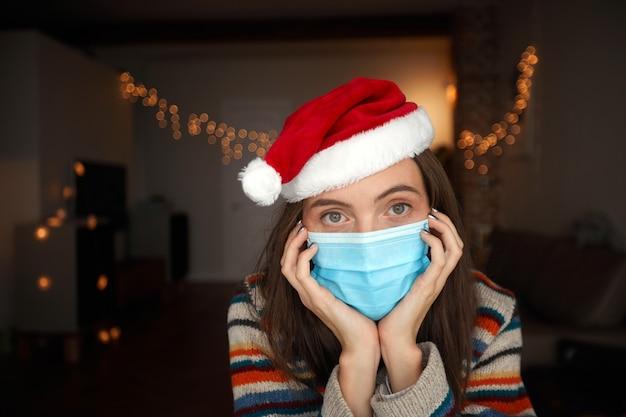 Женщина в медицинской маске и шляпе санта-клауса празднует рождество дома во время эпидемии