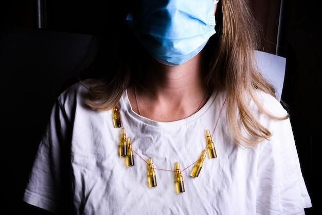 医療用マスクと白いtシャツの女性。医療アンプルの宝石を身に着けている女性。彼女の顔にサージカルマスクを持つ若い女性のクローズアップ