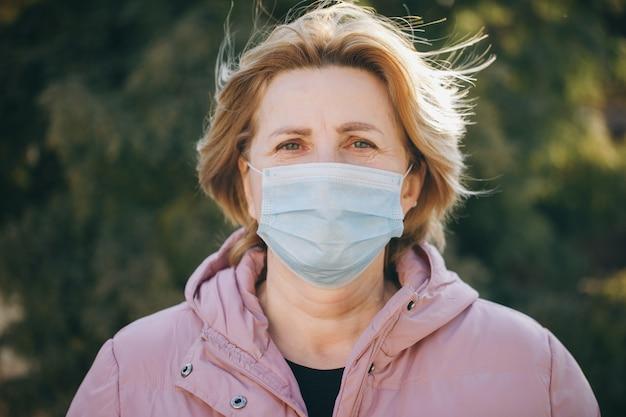 Женщина в медицинской маске. дышит глубоко на зеленом. здравоохранение и медицинская концепция
