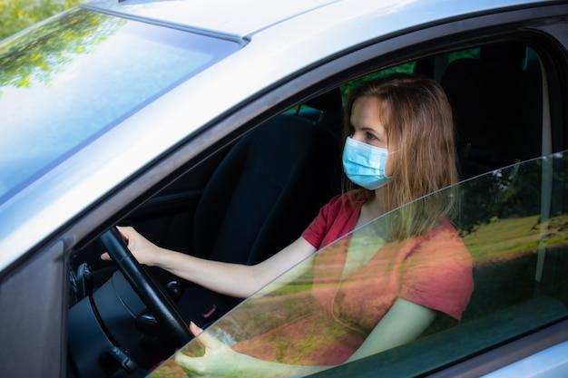 医療用マスクの女性が車を運転しています。コロナウイルスの時間。危険な状況。