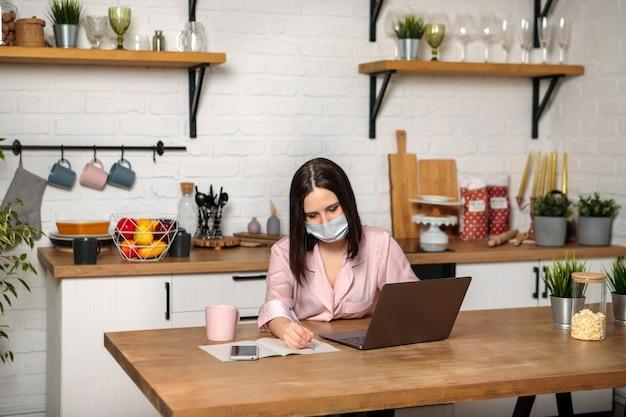 의료 마스크에 여자는 부엌에 집에서 원격으로 사무실에서 일하고 있습니다. 컴퓨터 사용. 원격 교육 온라인 교육 및 업무