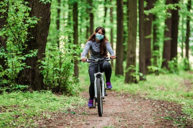 医療マスクの女性が公園で自転車に乗る