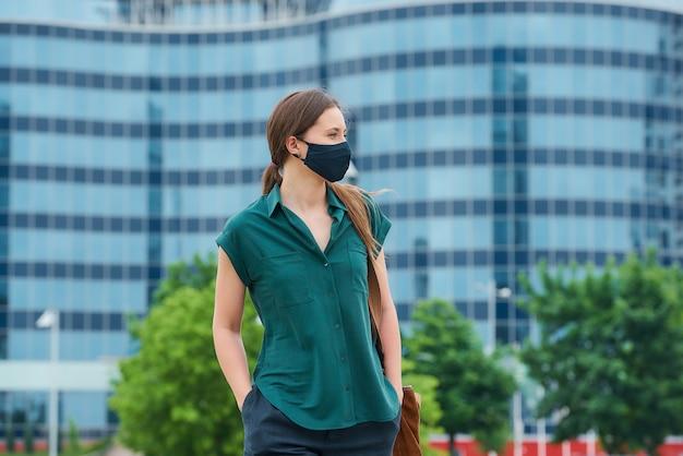 바지의 주머니에 밀어 넣는 의료 마스크에 여자