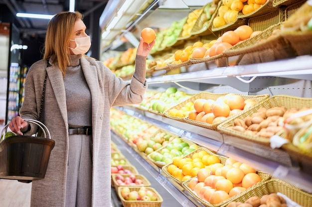 医療マスクの女性は、ウイルスのパンデミック中に食料品店で買い物をしています