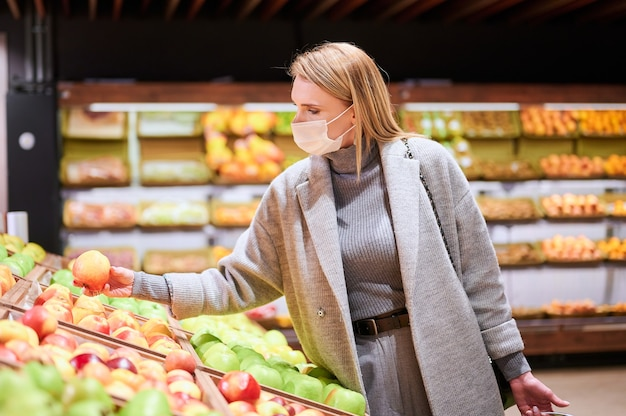 Женщина в медицинских масках делает покупки в продуктовом магазине во время пандемии вируса