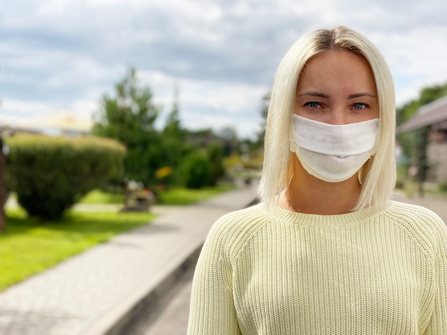 Женщина в маске медицинской защиты на открытом воздухе. копировать пространство