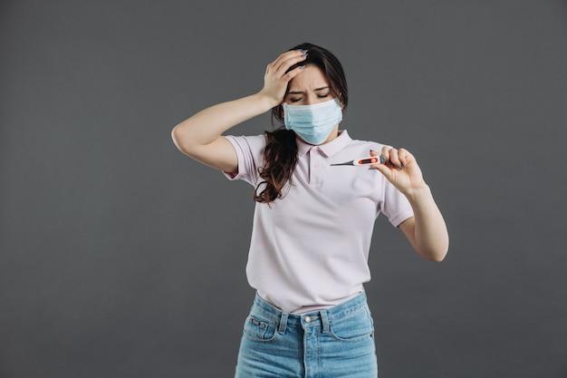 Женщина в медицинской защитной маске держит термометр, который показывает высокую температуру. симптомы коронавируса