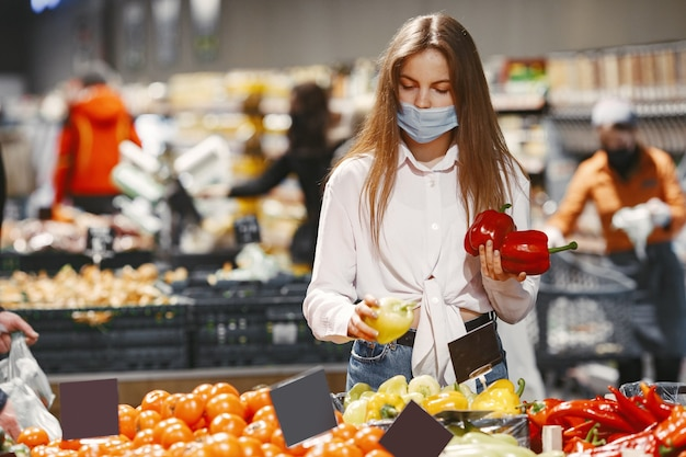 슈퍼마켓에서 의료 보호 마스크에 여자입니다.
