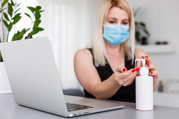 Женщина в медицинской защитной маске с антибактериальным антисептическим гелем для дезинфекции рук. профилактика здравоохранения во время вспышки вируса гриппа и эпидемии коронавируса