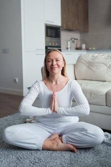 Женщина в позе медитации дома меня время и концепция благополучия