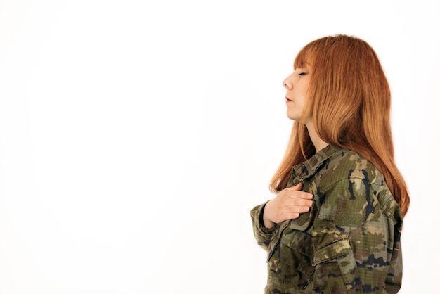 Женщина в военном камуфляже, стоя с закрытыми глазами