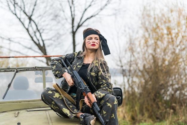 소총과 자동차와 군복을 입은 여자