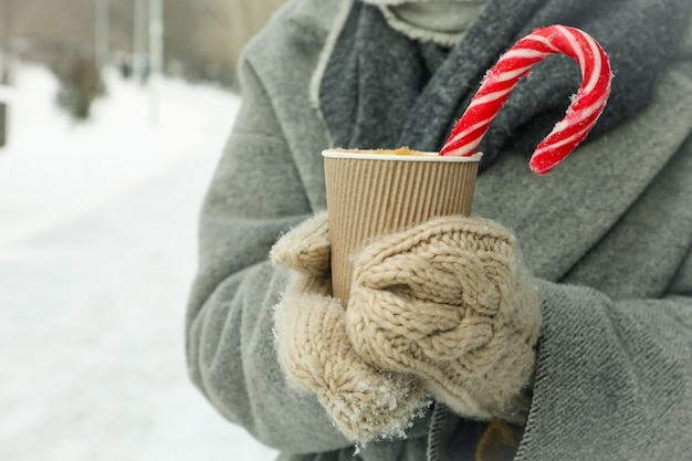 ミトンの女性は冬に屋外で温かい飲み物のカップを保持します