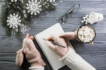 Woman in mittens writing in notebook near cup with marshmallow and eyeglasses