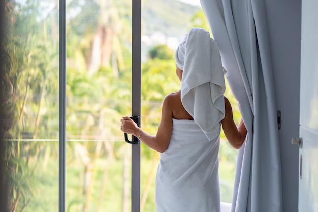 수건으로 샤워 한 후 아침에 여자가 발코니 문을 열고 열대 전망을 즐기기 위해 밖으로 나가십시오.