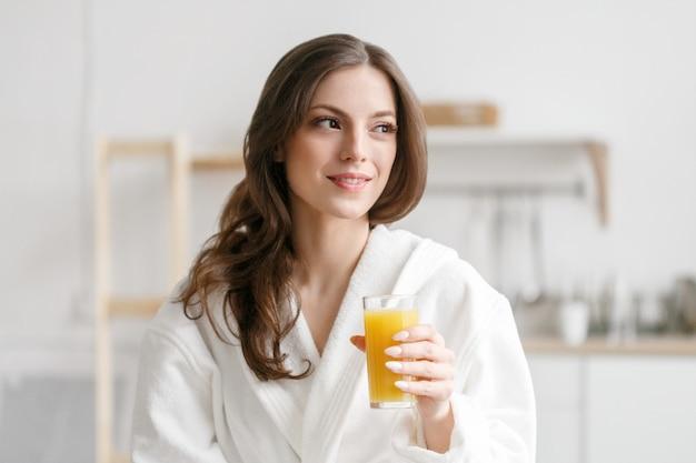 手に新鮮なオレンジジュースと朝の女性。朝食にオレンジジュースを飲む白いバスローブの女性ポジティブ完璧な朝の女性の肖像画。スタジオショット。