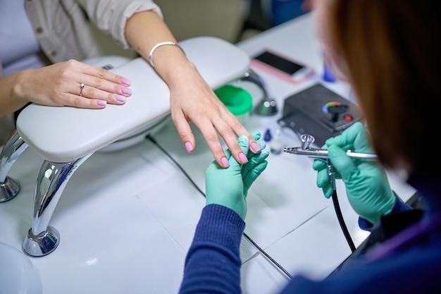 Женщина в салоне ногтей получает маникюр гель-лак мастером маникюра. бережный уход за ногтями