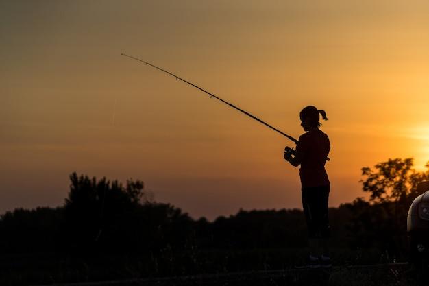 Женщина на природе, ловящая рыбу в живописном свете заката