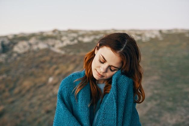 아침에 담요로 숨어있는 자연 속의 여성은 풍경을 감상한다