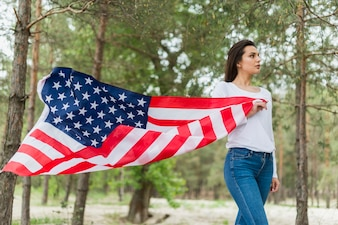 Woman in nature holding american flag