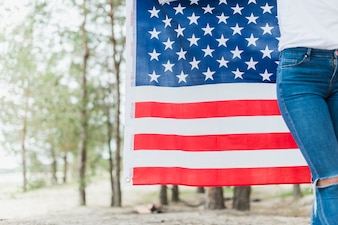 Woman in nature with american flag and copyspace