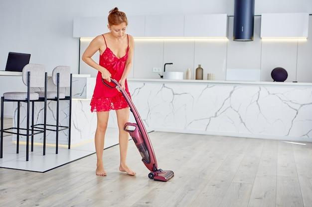 잠옷을 입은 여성이 수직 진공 청소기로 바닥을 청소합니다.