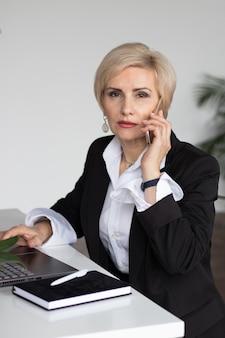 Женщина в офисе разговаривает по телефону