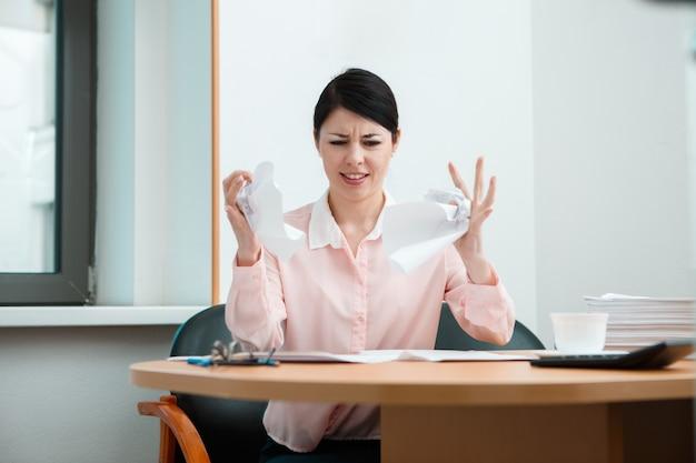 しわくちゃの紙でオフィスにいる女性。オフィスライフのコンセプト。