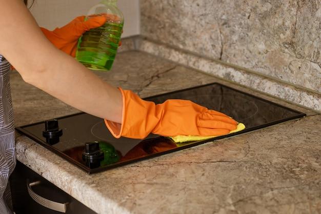 Женщина в оранжевых перчатках моет кухонную плиту тряпкой
