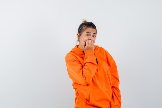 손톱을 물어뜯고 불안해 보이는 주황색 까마귀를 입은 여성