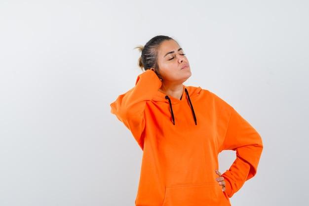 Женщина в оранжевой толстовке с капюшоном держит руку за головой и выглядит расслабленной