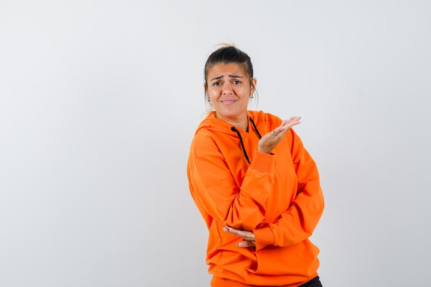 Женщина в оранжевой толстовке с капюшоном держит руку озадаченным жестом и выглядит недовольной