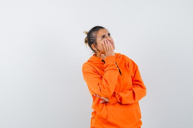 Женщина в оранжевой толстовке с капюшоном держит руку на щеке и выглядит задумчивой