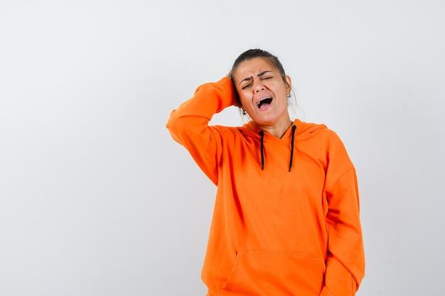 Женщина в оранжевой толстовке с капюшоном держит руку на голове и грустно смотрит