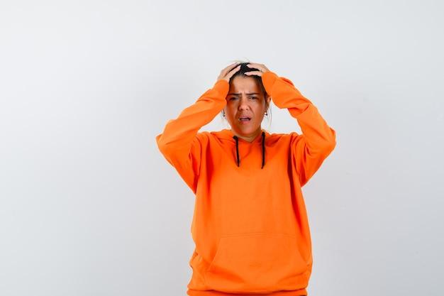 Женщина в оранжевой толстовке с капюшоном держит руки на голове и выглядит печально