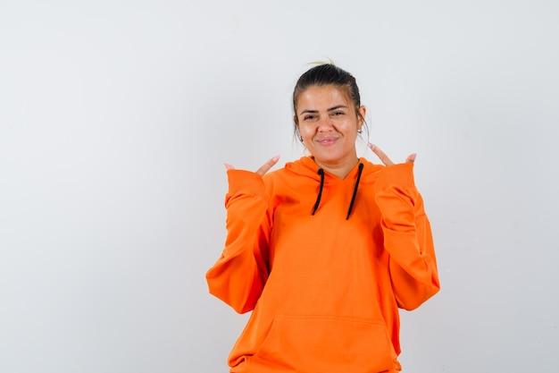 자신을 가리키며 행복해 보이는 주황색 까마귀를 입은 여자