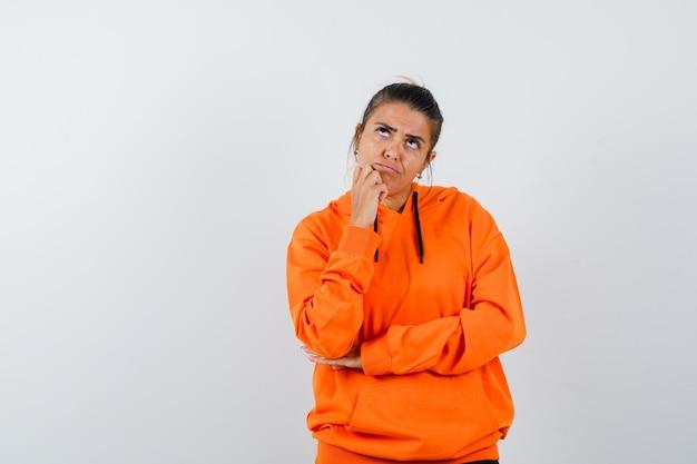 手に顎を支え、躊躇しているオレンジ色のパーカーの女性