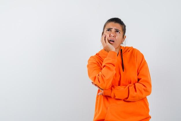 手に顎を支え、物思いにふけるオレンジ色のパーカーの女性